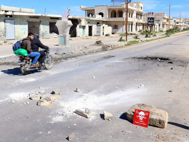 Men ride a motorbike past a hazard sign at a site hit by an airstrike in the town of Khan Sheikhoun. Photo: Reuters / Ammar Abdullah
