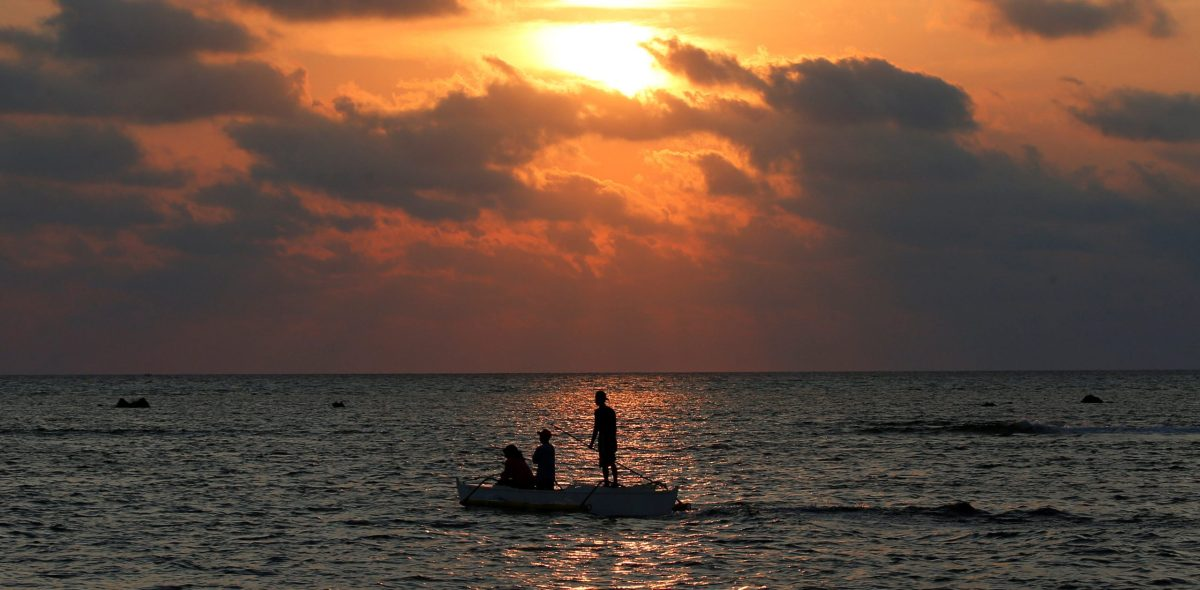 Philippine fishermen steer a dinghy during sunset in the disputed Scarborough Shoal. Photo: Reuters / Erik De Castro