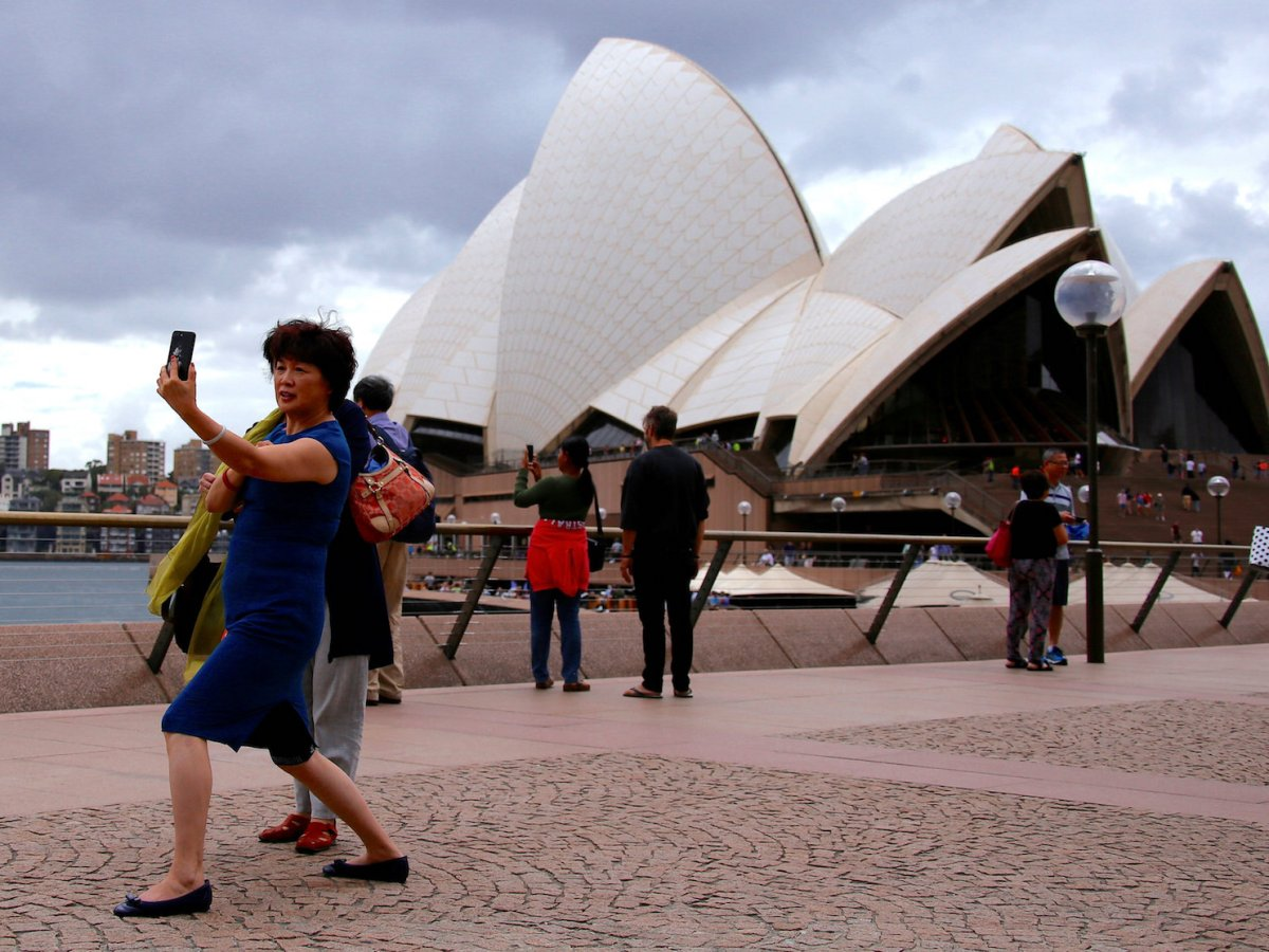 A Chinese tourist poses for a selfie in front of the Sydney Opera House on March 8, 2017. Some Chinese have been sold tickets to Australian tourist attractions obtained fraudulently on WeChat.  Photo: Reuters/David Gray