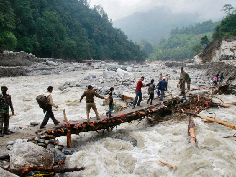 Indian army personnel help stranded people cross a flooded river after heavy rains in the Himalayan state of Uttarakhand Photo: Reuters