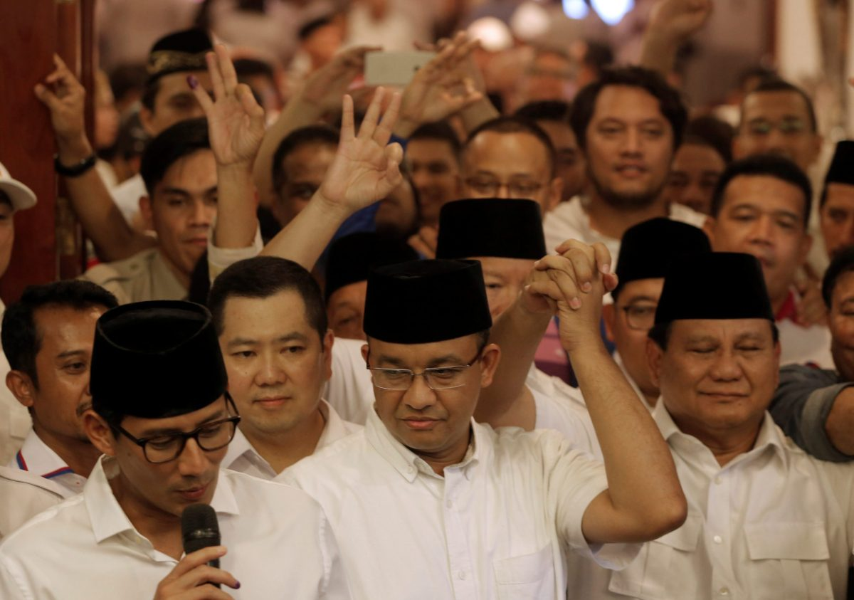 Former Indonesian education minister Anies Baswedan (C) holds the hand of Gerindra party chief Prabowo Subianto (R) as Baswedan running mate Sandiaga Uno (L) talks to reporters after voting in the Jakarta governor election in Jakarta, Indonesia April 19, 2017. Photo: Reuters/Beawiharta