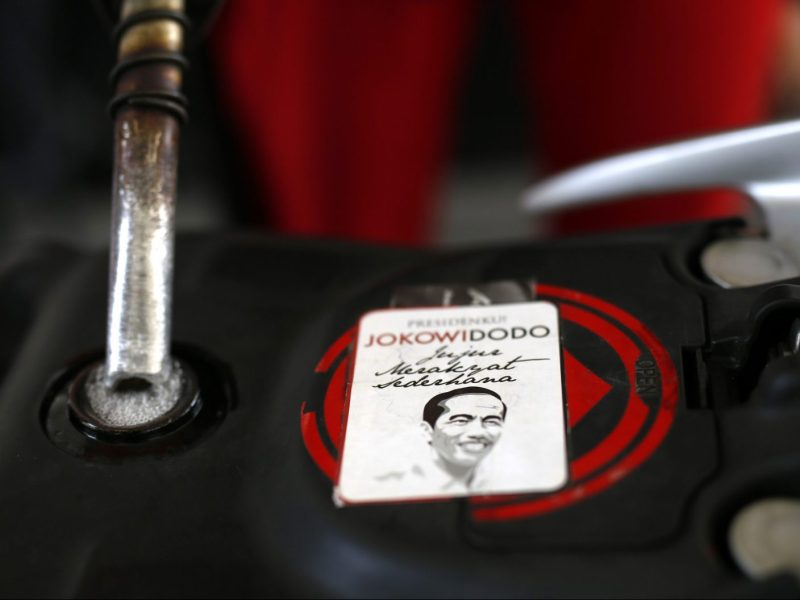 An election sticker with the image of new Indonesian President Joko Widodo is seen on a motorcycle gas tank as it is filled with subsidised fuel at a state-owned Pertamina petrol station in Jakarta October 31, 2014. Indonesia's new government will make changes to its costly gasoline and diesel subsidies before the end of the year, the country's chief economics minister said on Thursday. An advisor to Widodo, who was sworn in on Oct. 20, told Reuters earlier this month that a fuel price hike of 3,000 rupiah was planned by the new government, possibly as early as Nov. 1. REUTERS/Darren Whiteside (INDONESIA - Tags: POLITICS ENERGY BUSINESS) - RTR4C9YL
