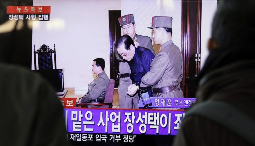 People watch television news showing Jang Song-thaek in court before his excution on December 12, 2013. Photo: AFP/Woohae