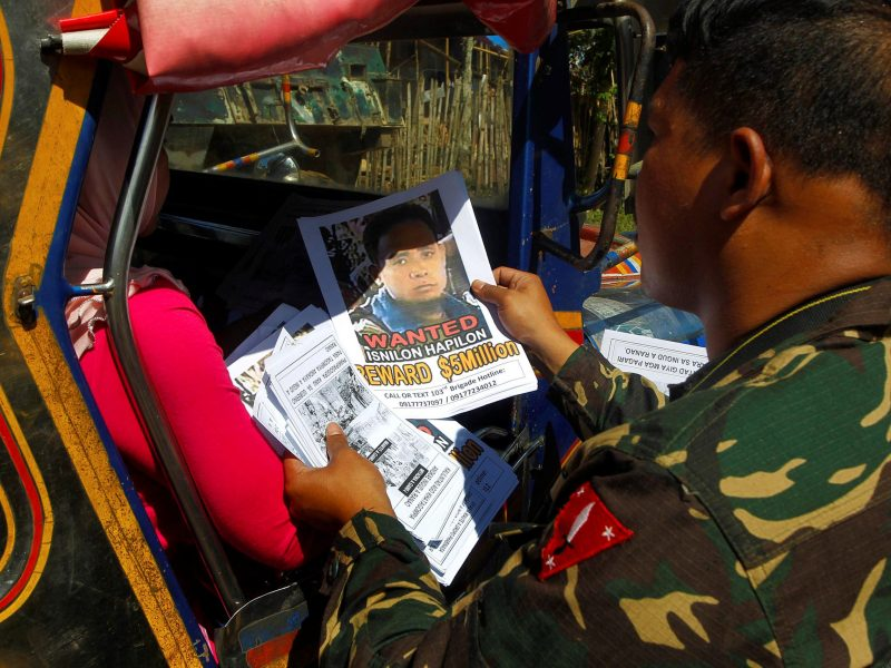 Soldiers distribute pictures of a member of extremist group Abu Sayyaf Isnilon Hapilon, who has a US government bounty of US$5 million for his capture in the southern Philippines. Picture taken February 1, 2017. Photo: Reuters/Marconi B Navales