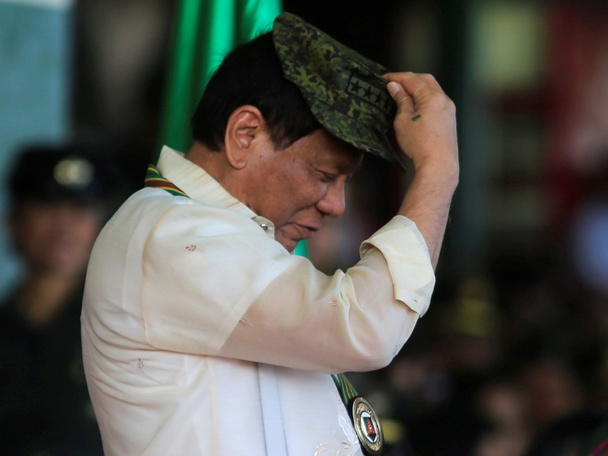 Philippine President Rodrigo Duterte tries on a military hat given to him during the 120th anniversary of the founding of the Philippine Army in Metro Manila on April 4, 2017. Photo: Reuters