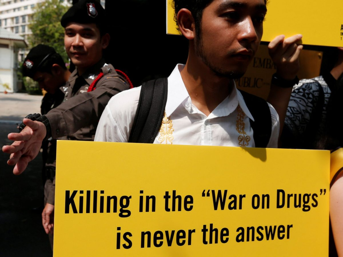 """An activist from Amnesty International Thailand holds a banner during a rally to urge the Philippines to stop """"War on Drugs"""" in front of Philippines' embassy in Bangkok, Thailand, April 25, 2017. REUTERS/Chaiwat Subprasom - RTS13RV0"""