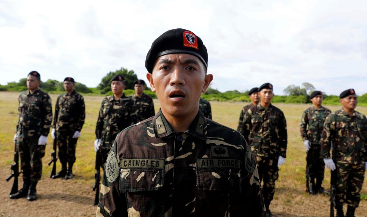 Filipino soldiers sing the national anthem in Philippine occupied (Pagasa) Thitu island in disputed South China Sea, April 21, 2017. REUTERS/Erik De Castro - RTS1393L