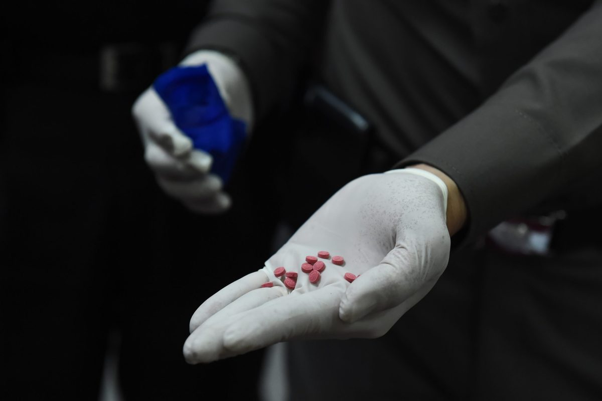 "A police officer displays ""yaba"" tablets, or methamphetamine mixed with caffeine, for the media in front of the Narcotics Suppression Division in Bangkok on February 1, 2017. Photo: AFP / Lillian Suwanrumpha"