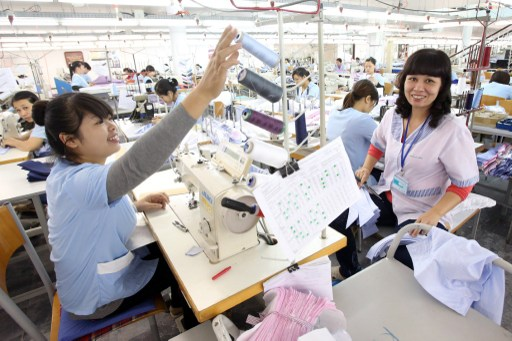 Employees sit at sewing machines in a textile factory in Hanoi, Vietnam. Photo: DPA, Bodos Marks