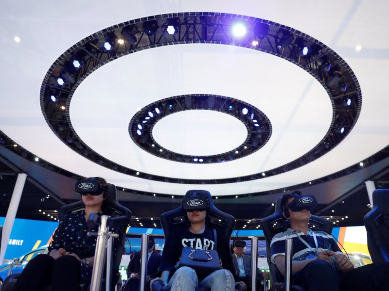 Visitors wear virtual-reality goggles at the Ford booth at the Shanghai Auto Show on April 20, 2017. VR technology is also becoming popular in the tourism industry. Photo: Reuters/Aly Song