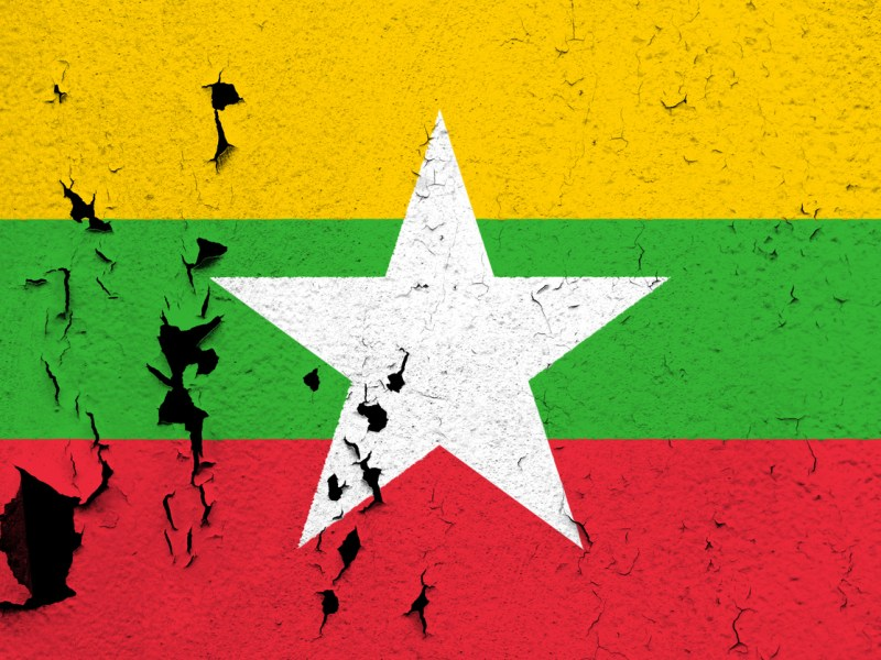 The flag of Myanmar painted on a cracked and peeling wall. Photo: Getty Images