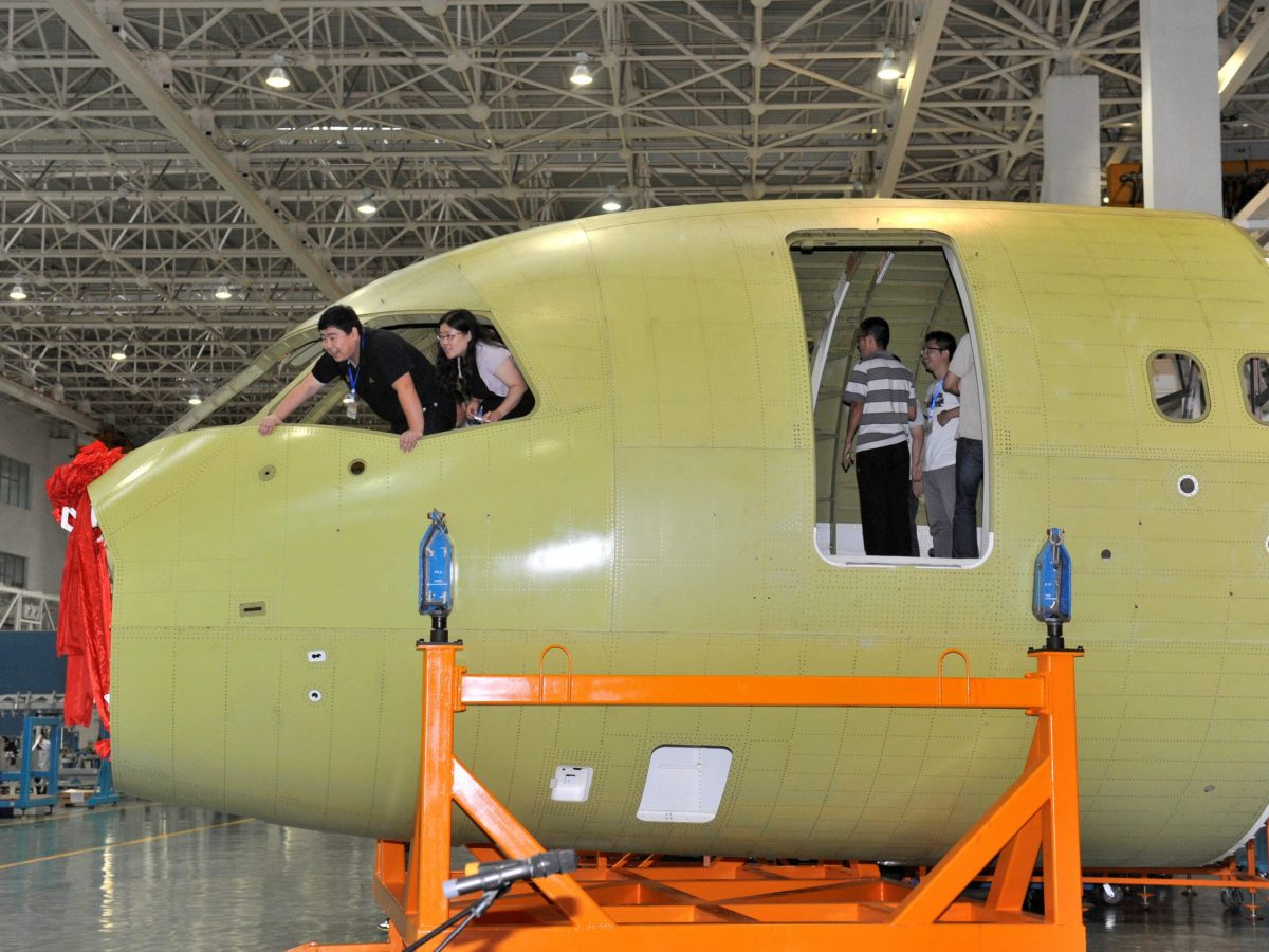 A file photo shows technicians inspecting the interior of a nose of China's home-grown airliner C919. Photo: Reuters via China Daily