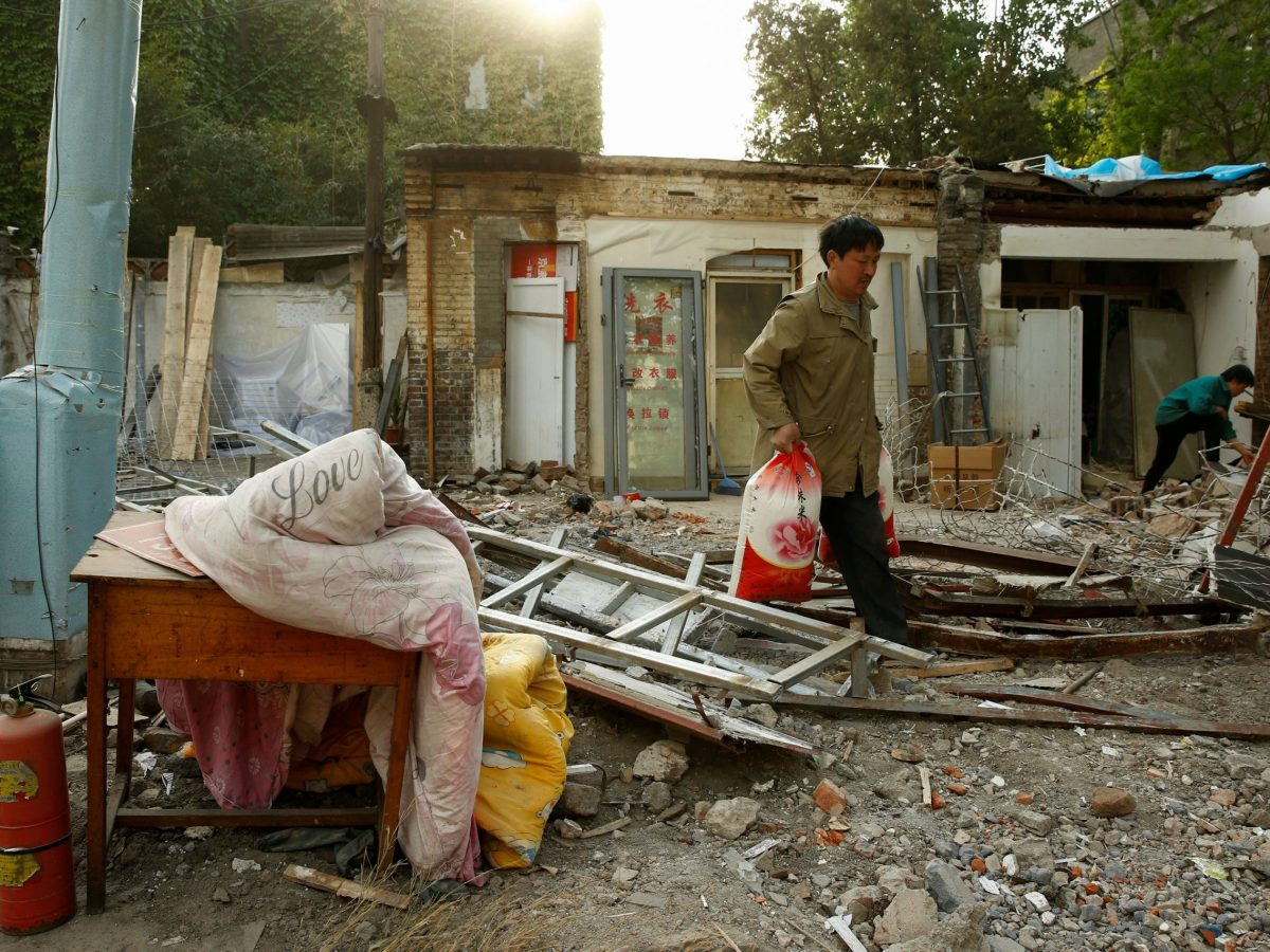 Sacked. A man carries sacks from a razed house in a hutong. Photo: Reuters/Thomas Peter