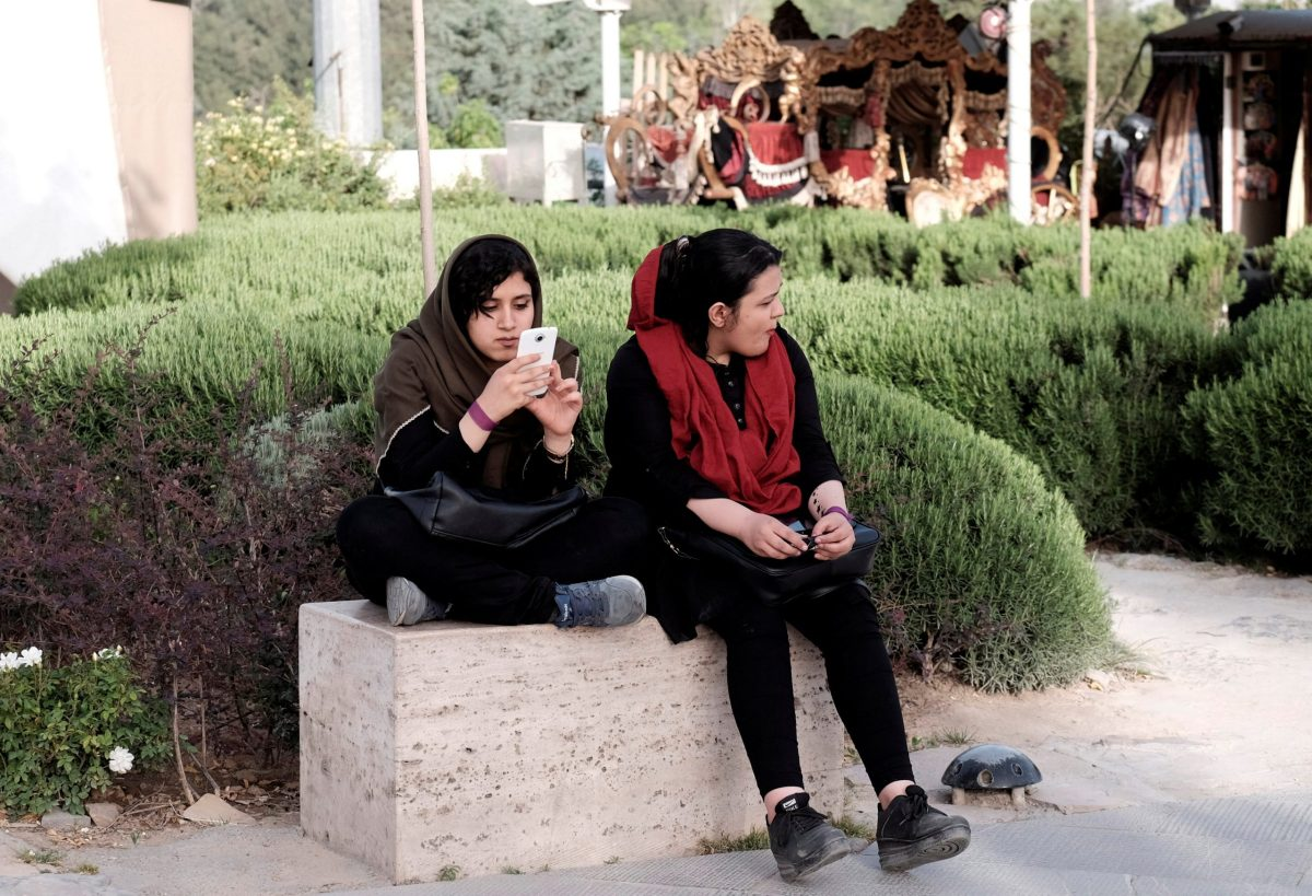 An Iranian woman uses her mobile phone as she rests at a park in Tehran, Iran, May 16, 2017. Photo: Reuters
