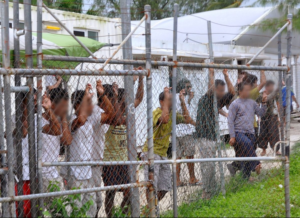 Asylum-seekers look through a fence at the Manus Island detention center in Papua New Guinea. Faces have been pixellated at source. Photo: Eoin Blackwell/AAP via Reuters