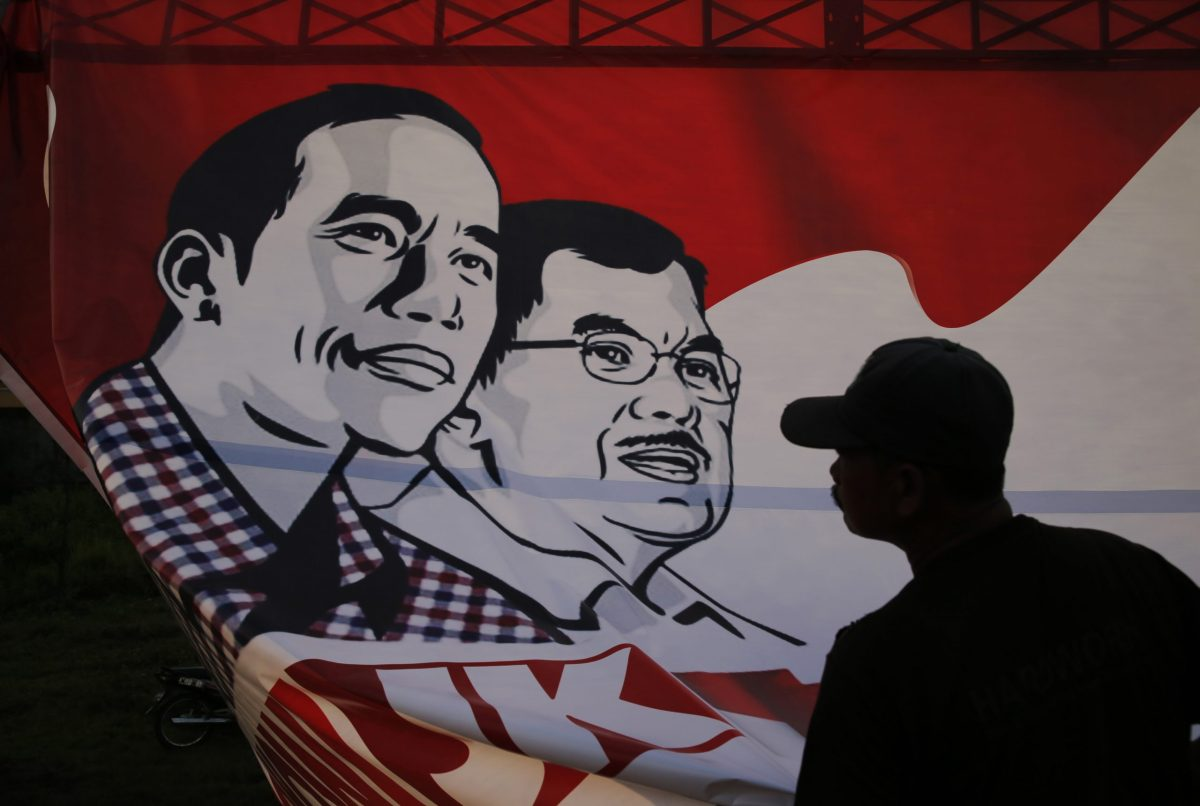 A worker pulls down a campaign poster of Indonesia's then presidential candidate Joko Widodo and his running mate Yusuf Kalla after a rally in Cirebon, Indonesia, June 18, 2014. Photo: Reuters/Beawiharta
