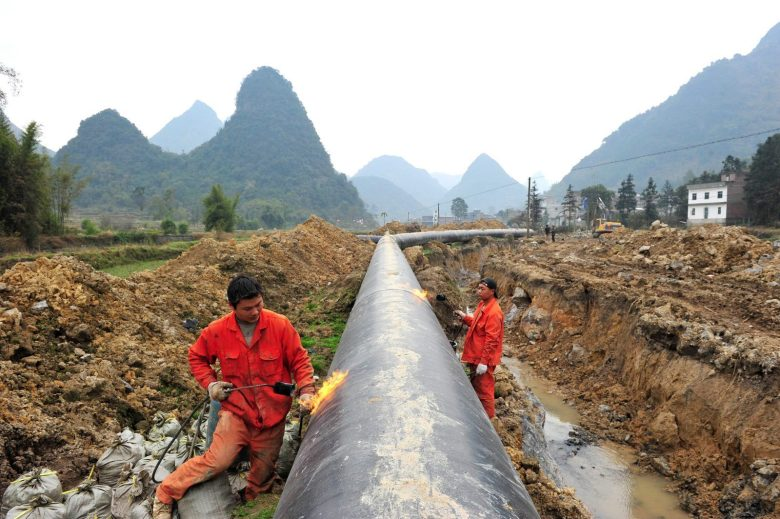 --FILE--Workers weld a pipeline at a construction site of the Myanmar-China natural gas pipeline in Laibin city, south Chinas Guangxi Zhuang Autonomous Region, 25 January 2013. The Myanmar-China natural gas pipeline was completed on Oct 20 2013, further diversifying Chinas sources of fuel from abroad and ensuring its energy security. The 2,520-kilometer pipeline starts at Kyaukpyu on Myanmars western coast, enters China at Ruili in Yunnan province and ends at Guigang in the Guangxi Zhuang autonomous region. It will provide natural gas to the southwestern provinces of Guangxi, Yunnan and Guizhou. The pipeline, on which construction began in June 2010, has an annual delivery capacity of 12 billion cubic meters, and will deliver 10 billion cu m a year. For the three Chinese provinces receiving the natural gas, the benefits will include cheaper domestic prices and greater energy supplies to the fuel industry.