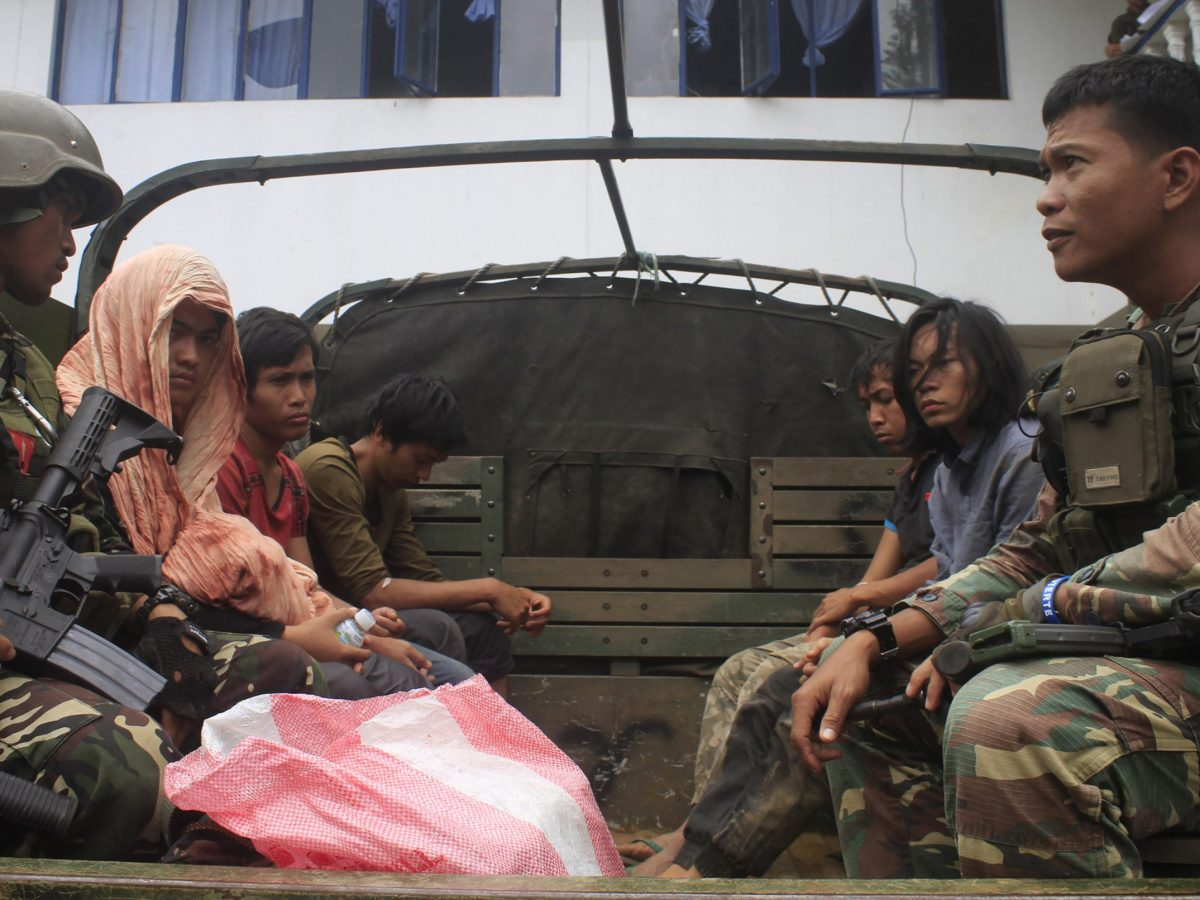 Philippine soldiers guarding members of the extremist Maute Group aboard a military vehicle in Marawi City in the southern island of Mindanao, a day after they were arrested at a military checkpoint and who were later on August 27, 2016 freed by their comrades in a daring jailbreak. Photo: AFP/Richele Umel