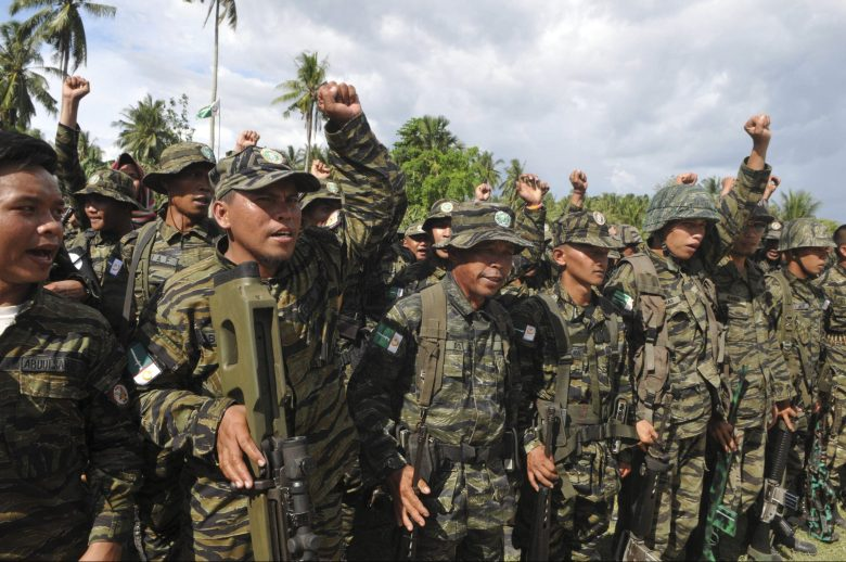 Moro Islamic Liberation Front (MILF) forces raise their fists during a show of force inside the camp in Camp Darapanan, Maguindanao province, southern Philippines March 27, 2014. The Philippines and its largest Muslim rebel group, the Moro Islamic Liberation Front (MILF), on Thursday signed a final peace pact, ending about 45 years of conflict that has killed more than 120,000 people in the country's south. REUTERS/Stringer (PHILIPPINES - Tags: POLITICS MILITARY) - RTR3ITSE