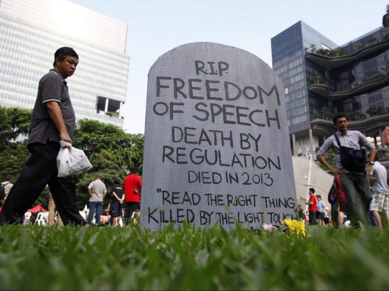 "Protesters walk past a mock gravestone that reads ""RIP Freedom of Speech"" during a protest against new licensing regulations imposed by the government for online news sites, at Hong Lim Park in Singapore June 8, 2013. Photo: Reuters"