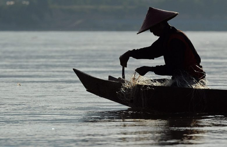 TO GO WITH Thailand-SEAsia-environment-dam,FEATURE by Amelie Bottollier-DepoisThis picture taken on May 29, 2013 shows a fisherman sitting on his boat as he pulls his net from the Mekong river in Wiang Kaen, a district in the northern Thai province of Chiang Rai bordering Laos. The waters of the mighty Mekong have sustained generations of families but nowadays its fishermen often find their nets empty and fear hydropower mega-dams will destroy their livelihoods. AFP PHOTO / Christophe ARCHAMBAULT / AFP PHOTO / CHRISTOPHE ARCHAMBAULT