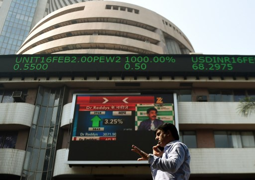 An Indian man speaks on a phone as he walks by stock prices in Mumbai. Photo: AFP Punit Paranjpe