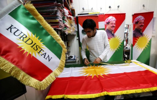 A man sews an Iraqi Kurdish flag that will bear a portrait of Iraqi Kurdish leader Massud Barzani. Photo: AFP / Safin Hamed