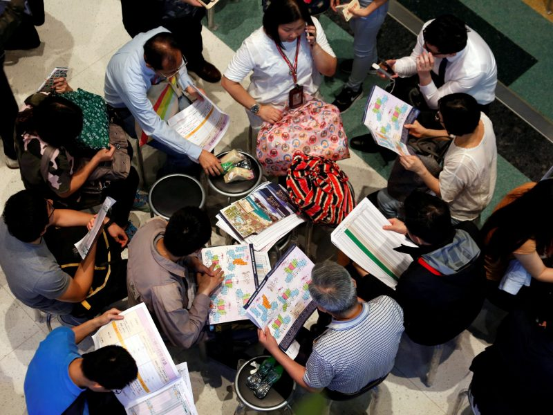 Buyers study floor plans and price lists. Photo: Reuters/Bobby Yip