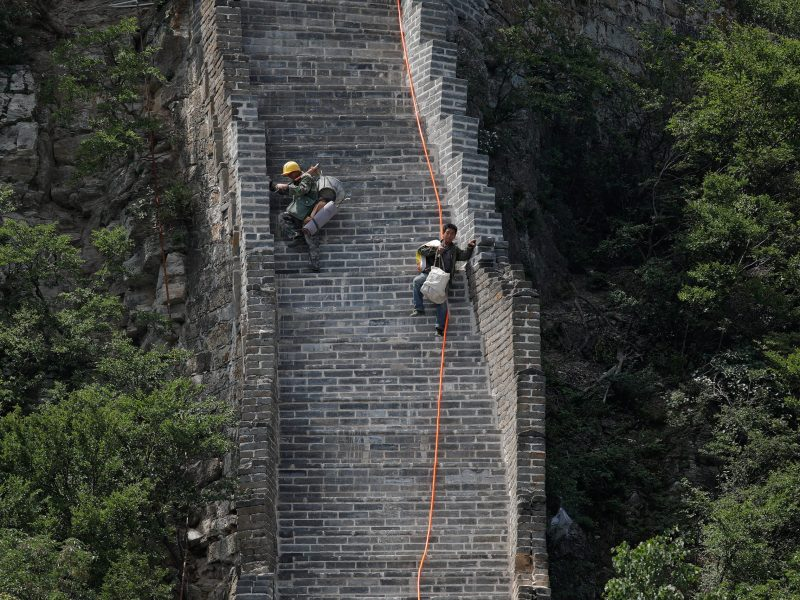 Workers carry their tools and belongings as they climb down the Jiankou section of the Great Wall. Photo: Reuters/Damir Sagolj