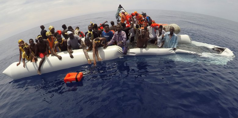 """Migrants on a sinking dinghy wait to be rescued by """"Save the Children"""" NGO crew from the ship Vos Hestia in the mediterranean . Photo: Reuters/Stefano Rellandini"""