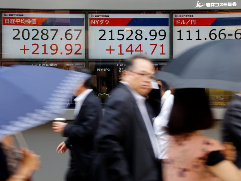 People walk past an electronic board showing Japan's Nikkei average (left), the Dow Jones average (center), and the exchange rates between the Japanese yen and the US dollar outside a brokerage in Tokyo, Japan. Photo: Reuters / Toru Hanai