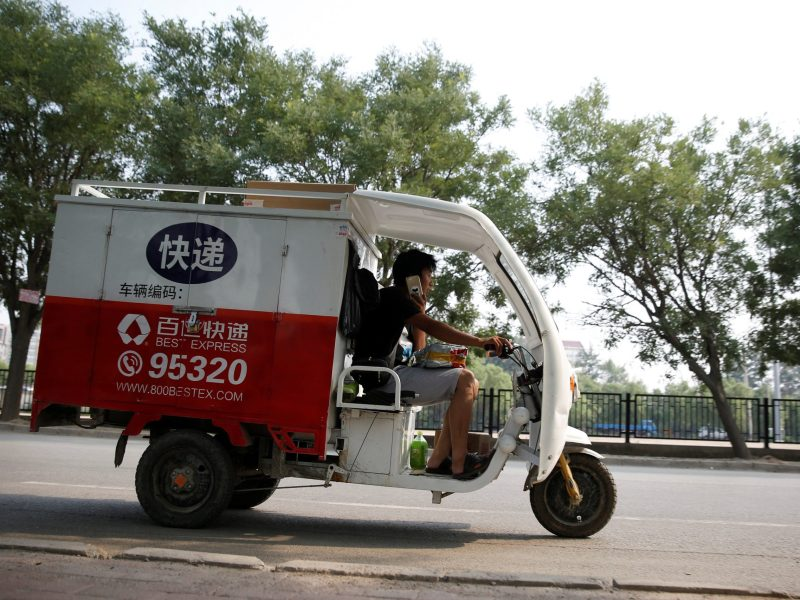 A man rides an electric delivery vehicle of the Chinese logistics company Best Inc in Beijing. Photo: Reuters/Thomas Peter