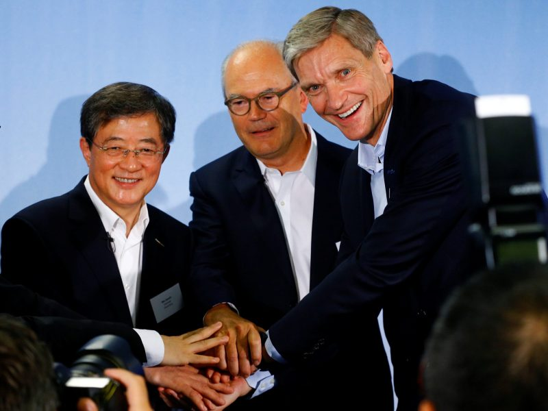 Syngenta chief executive Erik Fyrwald and Syngenta Chairman Michel Demare shake hands with ChemChina Chairman Ren Jianxin in Basel. Photo: Reuters/Arnd Wiegmann