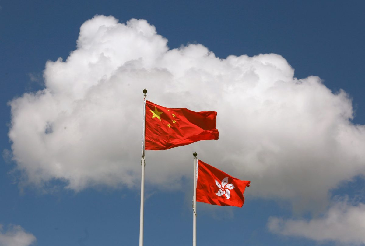 A Chinese national flag (L) and a Hong Kong flag fly outside the Legislative Council, three days before the territory celebrates the 20th anniversary of its handover to Chinese rule, in Hong Kong, China June 28, 2017. REUTERS/Bobby Yip