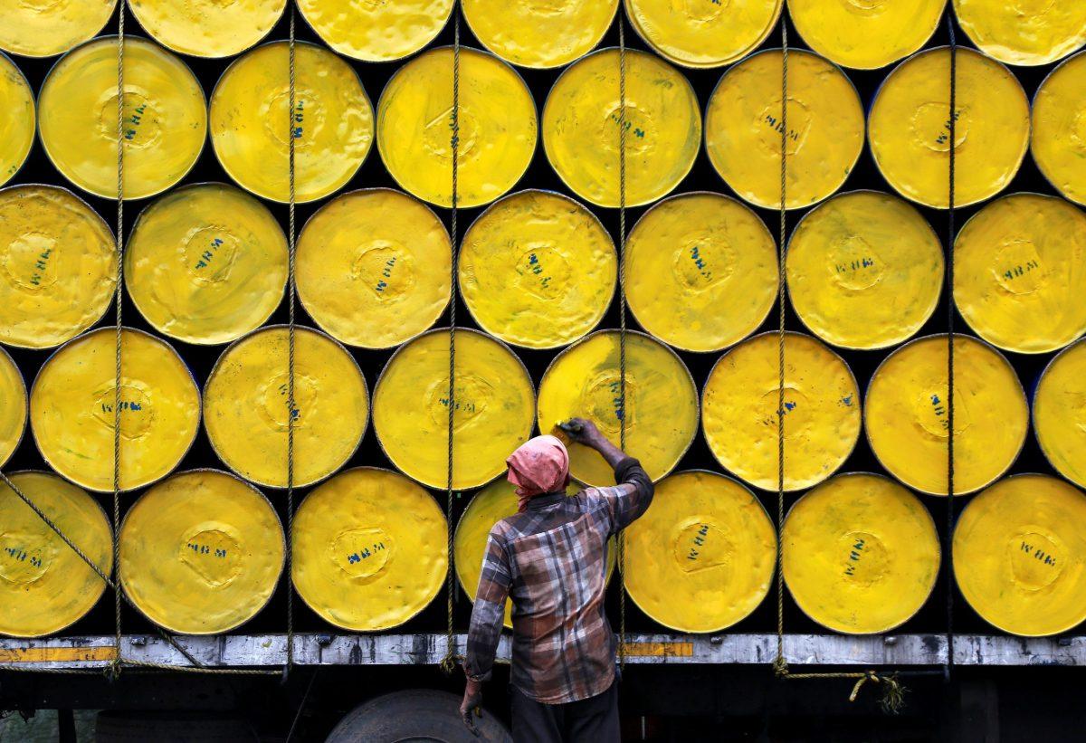 A worker paints empty barrels loaded onto a truck at a roadside in Kochi, India on June 29, 2017. Photo: Reuters / Sivaram V