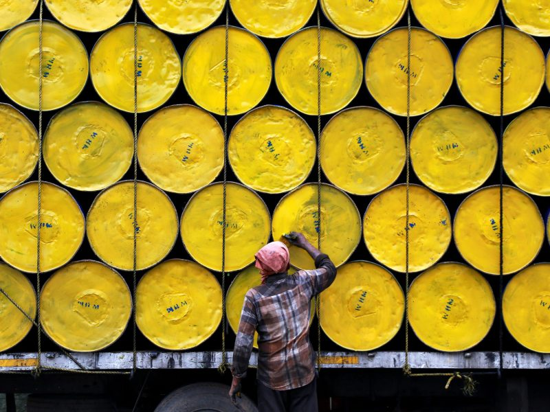 A worker paints empty barrels loaded onto a truck at a roadside in Kochi, India on June 29, 2017. Photo: Reuters / Sivaram V