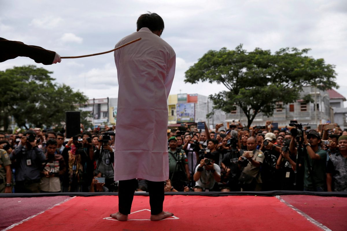 An Indonesian man is publicly caned for having gay sex, in Banda Aceh, Aceh province, Indonesia. Photo: Reuters/Beawiharta