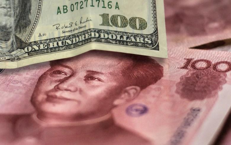 100 US dollar bill and 100 China yuan banknote.
