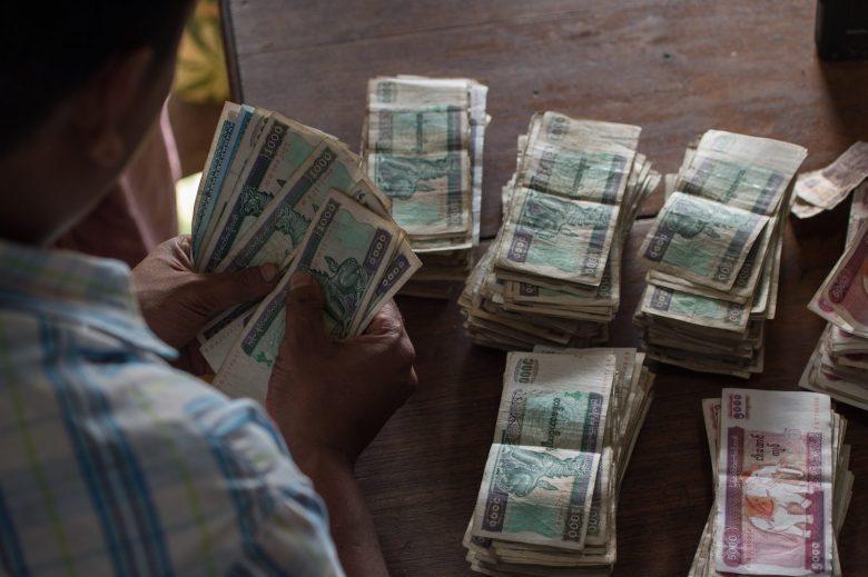 A Myanmar man counts his money at a market in Yangon on April 19, 2017. Photo: AFP/Roberto Schmidt