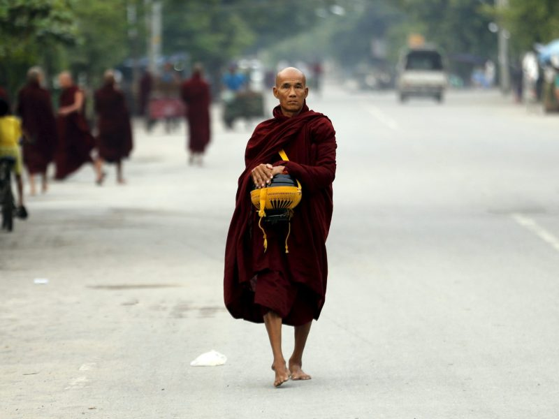 A Buddhist monk walks with his alms bowl early morning in the Myanmar city of Mandalay. Photo: Reuters/Jorge Silva