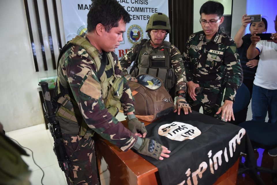 """Philippine Army troopers, assisted by military spokesperson in Marawi Lieutenant Colonel Jo-Arr Herrera (R), prepare to display an ISIS flag and 11kg of the illegal drug """"shabu"""", which were recovered from an Islamist militants' position prior to a press conference at the provincial capitol in Marawi on the southern island of Mindanao on June 19, 2017.Hundreds of Islamist militants -- supported by foreign fighters -- rampaged through Marawi, the largely Christian Philippines' most important Muslim city, on May 23 waving black flags of the Islamic State (IS) group. Duterte declared martial law in Mindanao to counter the attack, which he said was part of a plan by IS to establish a base in the country. / AFP PHOTO / Ted ALJIBE"""