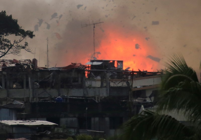 Debris and fire is seen after an OV-10 Bronco aircraft released a bomb, during an airstrike, as government forces continue their assault against insurgents from the Maute group, who have taken over large parts of Marawi City, Philippines. Photo: Reuters/Romeo Ranoco