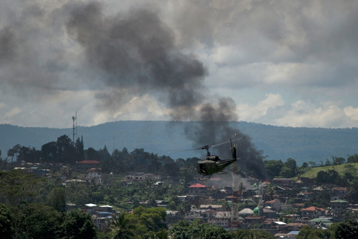 A helicopter flies through smoke billowing from houses after aerial bombings by Philippine Airforce planes on Islamist militant positions in Marawi on the southern island of Mindanao on June 17, 2017. Photo: AFP/ Noel Celis