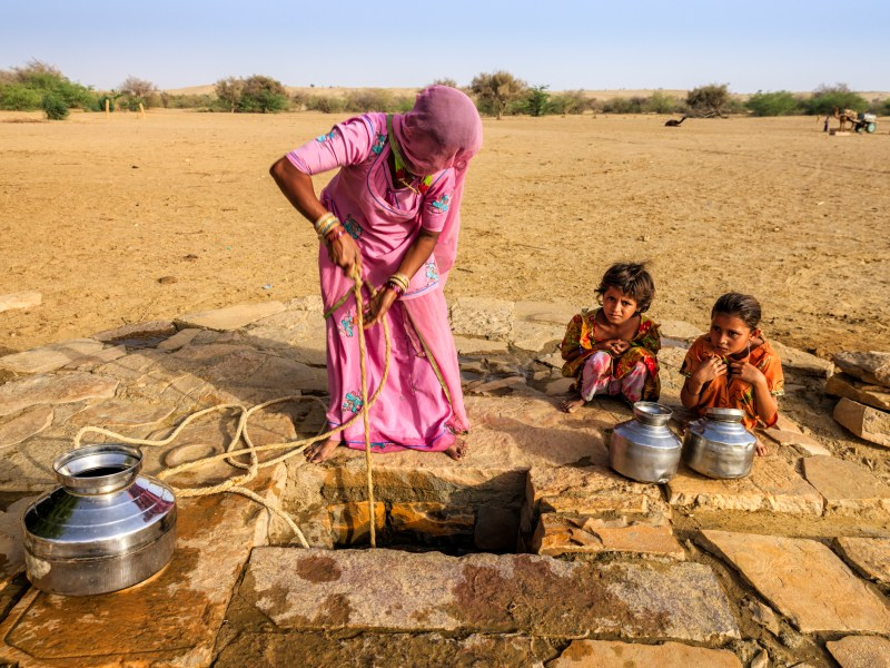 Indian woman drawing water from the well as two of her children wait in the  Thar Desert, Rajasthan. Photo: iStock