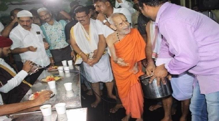 Vishwesha Tirtha Swami serves dates to Muslims in Udupi on Saturday. Photo: The News Minute