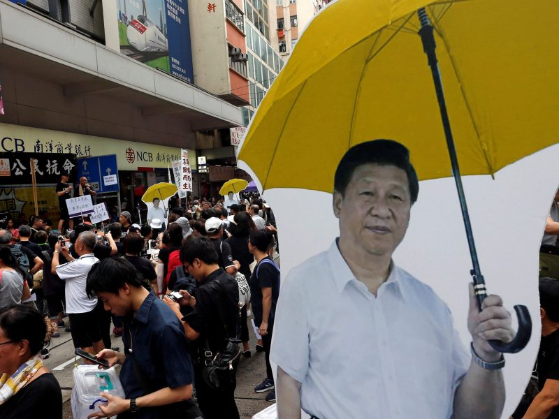 Cutouts of Chinese President Xi Jinping and yellow umbrella, symbol of the Occupy Central civil disobedience movement, are seen during a march on the day marking the 20th anniversary of Hong Kong's handover to Chinese sovereignty from British rule, in Hong Kong, China July 1, 2017. REUTERS/Tyrone Siu   NO RESALES. NO ARCHIVES