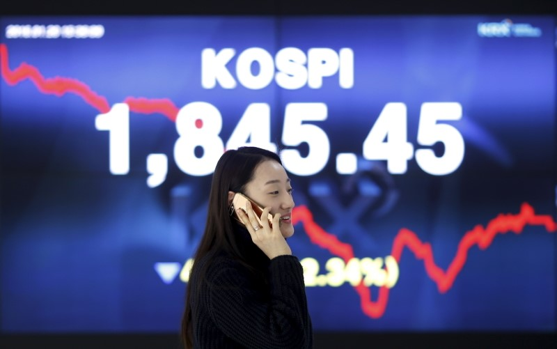 A woman talking on the phone walks past an electronic board of the Korea Composite Stock Price Index (KOSPI) at the Korea Exchange (KRX) in Seoul, South Korea, January 20, 2016  REUTERS/Kim Hong-Ji