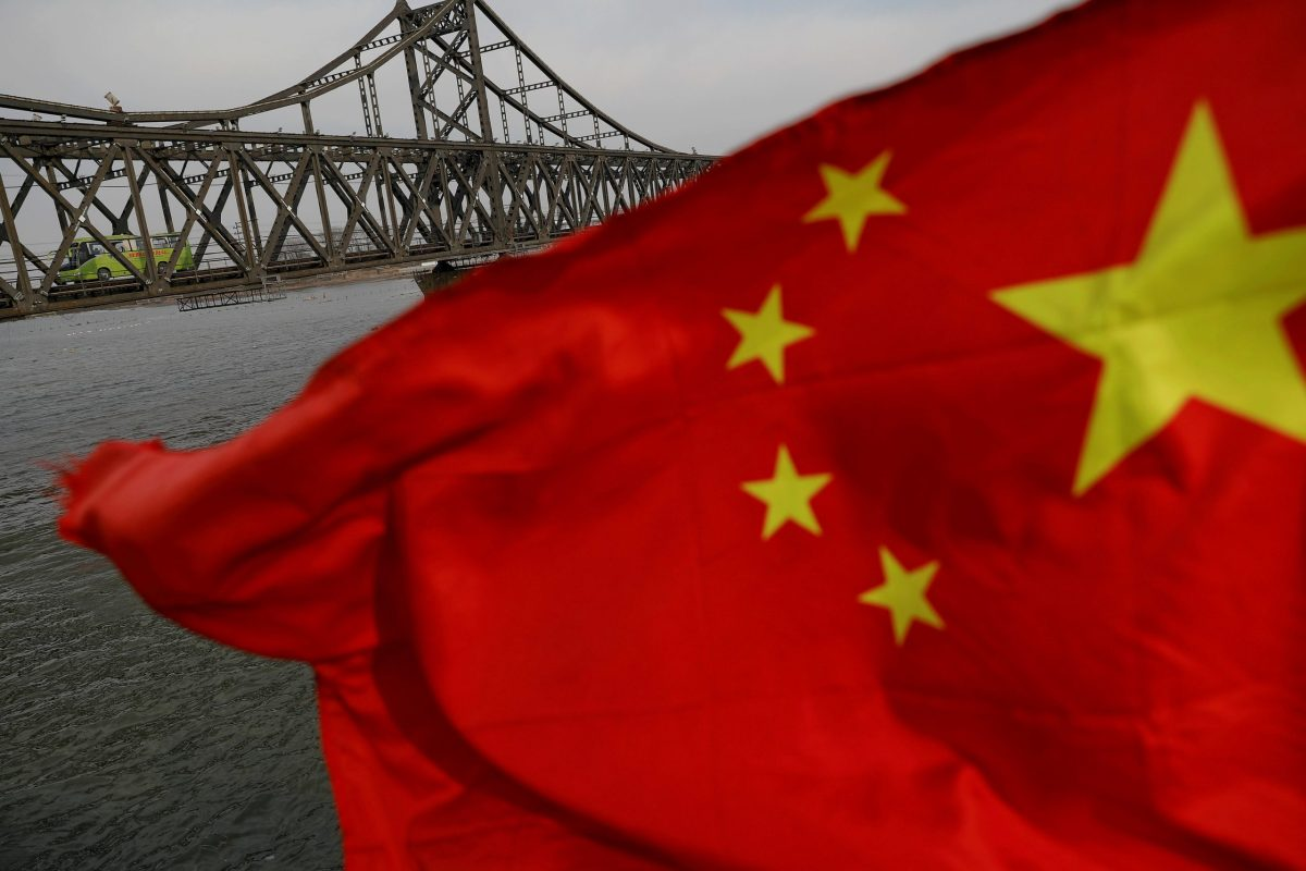 A Chinese flag in front of the Friendship bridge over the Yalu River connecting North Korea and China. Photo: Reuters/Damir Sagolj