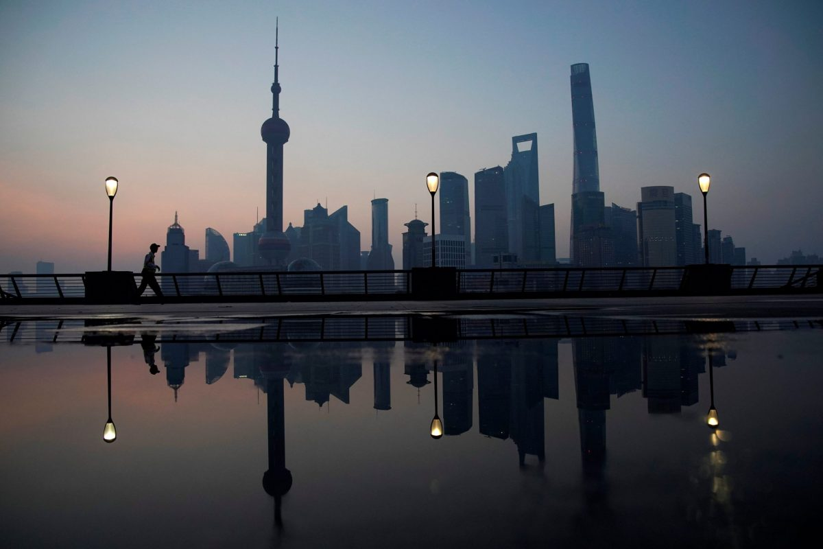 A security guard walks on the bund in front of the financial district of Pudong in Shanghai. Photo: Reuters/Aly Song