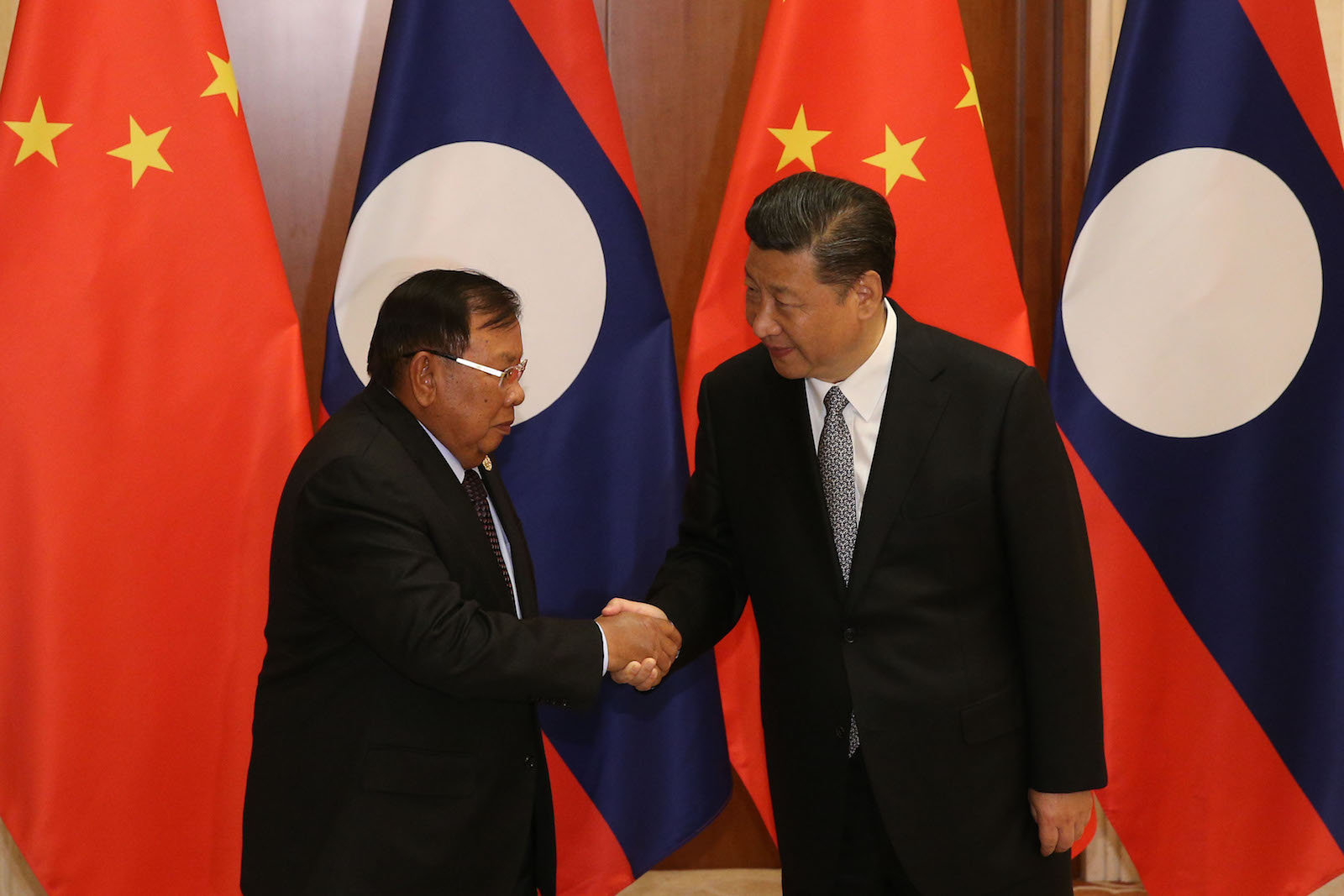 Laos' President Bounnhang Vorachith (L), shakes hands with Chinese President Xi Jinping (R) ahead a bilateral meeting at Diaoyutai State Guesthouse in Beijing on May 16, 2017.   / AFP PHOTO / POOL / WU HONG
